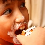 Photo of a child eating a cupcake