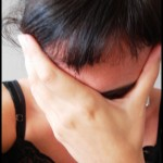 Photo of a depressed woman holding her face
