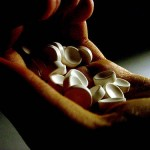 Photo of hand holding pills