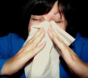 Photo of a woman sneezing into a hankie
