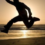 Photo of a man jumping for joy at eth seaside