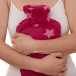 Photo of a woman's hands holdilng a hot water bottle to her abdomen