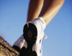 Photo of feet walking against blue sky backdrop
