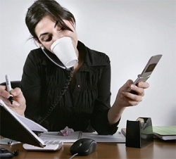 Photo of a woman multitasking at her desk