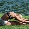 Photo of a woman doing yoga by a lake