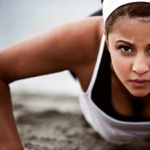 Photo of a woman doing push-ups on the beach