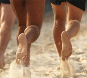 Photo of bare feet running on the sand
