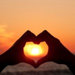 Photo of two hands making a heart shape aroudn the sun
