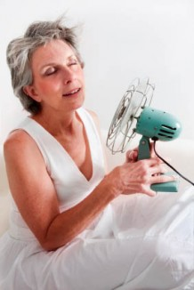 Photo of an older woman cooling herself off with a fan