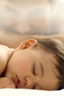 Photo of a baby boy sleeping with father in the background