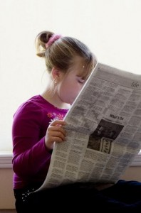 Photo of a child reading a newspaper