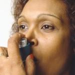 Photo of a woman using an asthma inhaler