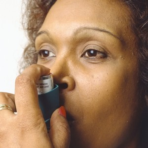 Photo of a woman using an asthma inhaler