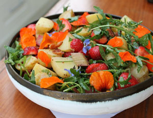 Photo of a potato salad with strawberries, bitter herbs and nasturtiums