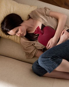 Photo of a woman with stomach cramps holding a hot wter bottle