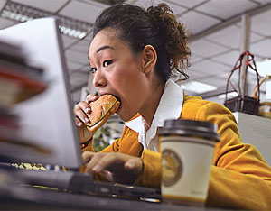 Photo of a woman eating at her desk