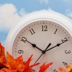 Photo of a clock sitting in autumn leaves