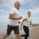 Photo of a man and a woman runnign on a beach