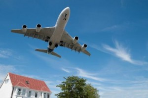 Photo of a jet aircraft flying over a house