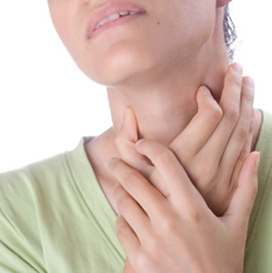 Photo of a woman holding a sore throat