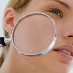 Photo of a woman holding a magnifying glass up to her skin