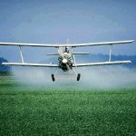 Photo of a airplane spraying pesticides on a field