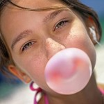 Photo of a girl chewing gum and blowing a bubble