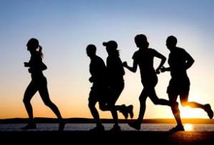 Photo of adults running at sunset