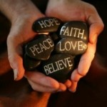 Photo of hands holding stones with spiritual messages written on them