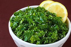 Photo of a bowl of kale with a lemon slice