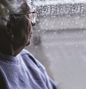 Photo of an older woman looking out of a window