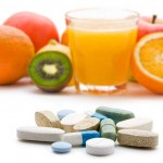 Photo of vitamins in foreground and fresh fruit in the background