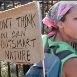 Photo of a woman carrying an anti-GMO protest sign on her back