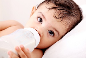 Photo of an infant drinking from a bottle