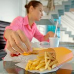Photo of a stressed woman eating junk food
