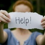 Depressed woman holding up a 'help' sign