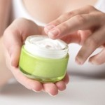 Photo of woman using face cream